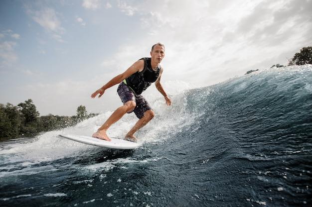 Uomo attivo che guida sul wakeboard bianco sull'onda alta