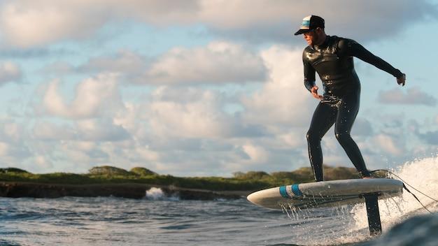 Uomo attivo in attrezzatura speciale che fa surf alle hawaii