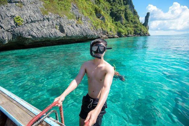 Un uomo attivo sulla barca longtail tradizionale tailandese è pronto per fare snorkeling e immersioni, isole phi phi, thailandia