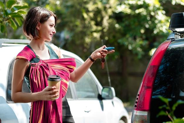 Mamma attiva chiude la macchina con un portachiavi per andare a fare una passeggiata nel parco con il suo bambino al collo
