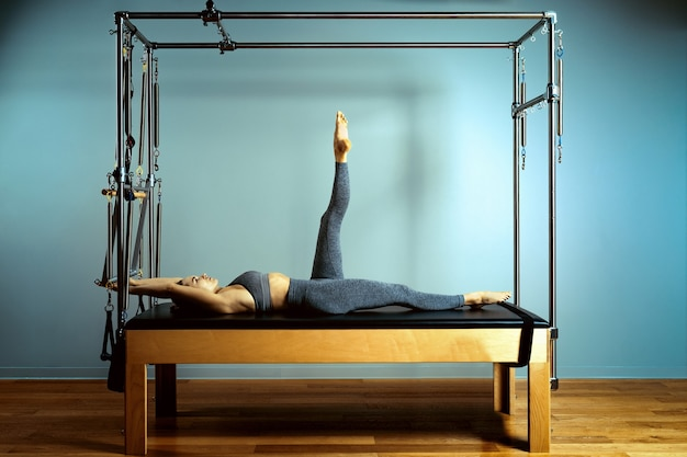 Donna motivata attiva fa esercizi a letto reformer, bellezza e salute. plastica, postura, fitness intelligente.