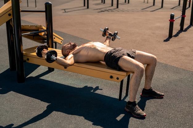 Ragazzo torso nudo muscolare attivo con bilancieri sdraiato sulla panca di legno mentre si esercita sul campo sportivo