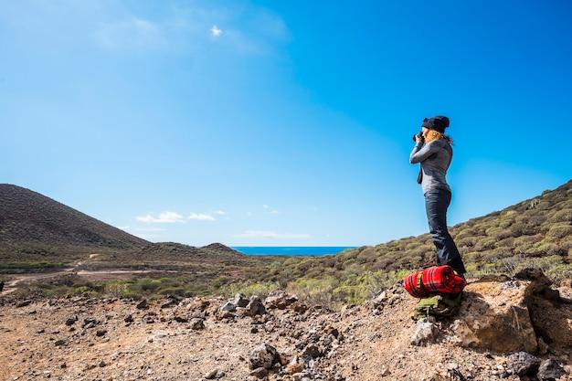 La gente attiva della natura all'aperto concepisce con la giovane donna in piedi con l'attrezzatura dello zaino e di trekking che prende un'immagine al bel paesaggio con la montagna e il mare della valle