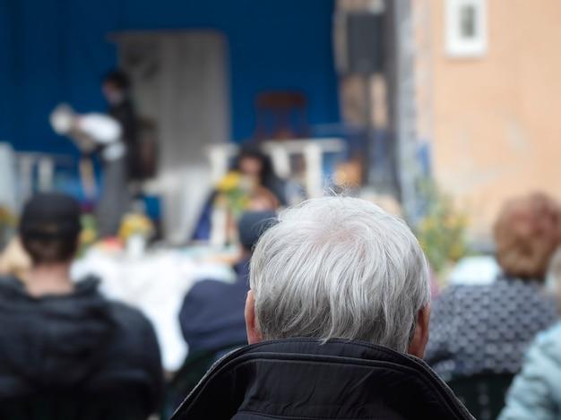 Un pensionato attivo ascolta opera. vista posteriore dell'uomo con la testa di capelli grigi all'aria aperta.