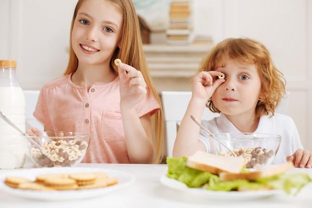 Fratelli attivi fantasiosi positivi seduti al tavolo e si divertono gustando gustosi spuntini al mattino