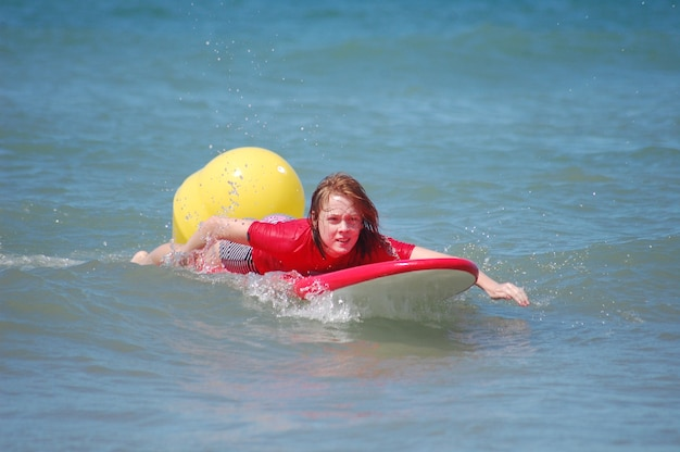 Ragazza dai capelli rossi attiva che pratica il surfing nel mare blu al sole