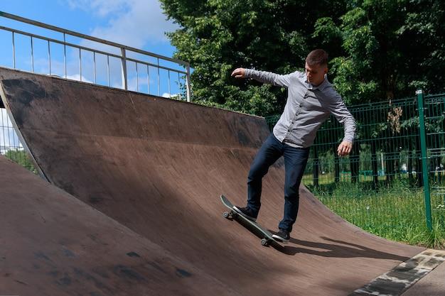 Riposo attivo nello skate park. ute guy hipster in camicia e jeans sta cavalcando uno scivolo da skateboard nel parco sullo sfondo di alberi e luce solare intensa