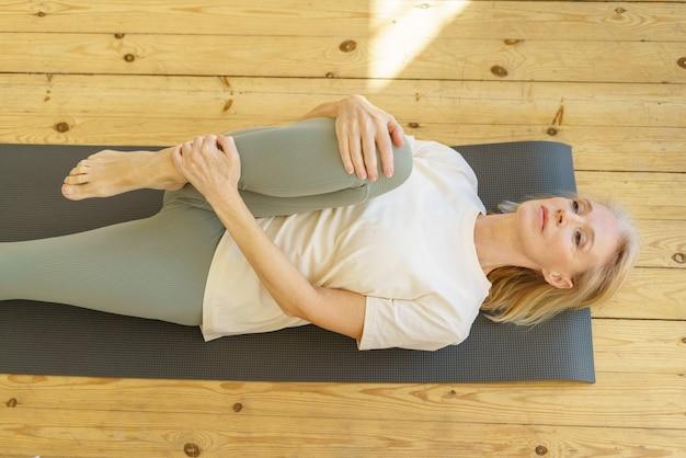 Donna in pensione attiva che fa esercizi di stretching al mattino sul tappetino da yoga a casa