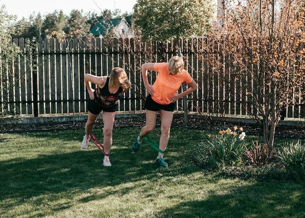 Le donne anziane attive di 55-59 anni eseguono esercizi per le gambe con elastici sportivi all'aperto
