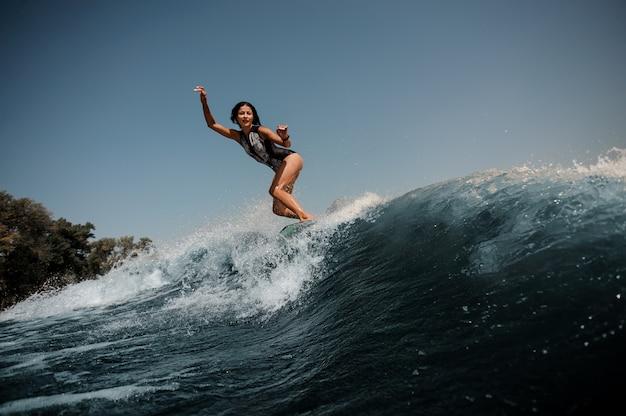 Donna castana sexy attiva che pratica il surfing a bordo giù l'acqua blu