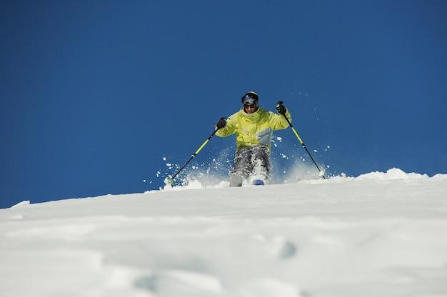 Sciatore attivo in abbigliamento sportivo giallo a cavallo lungo il pendio in georgia, gudauri