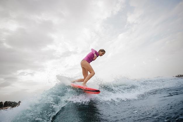 Ragazza esile attiva che guida sul wakeboard arancio