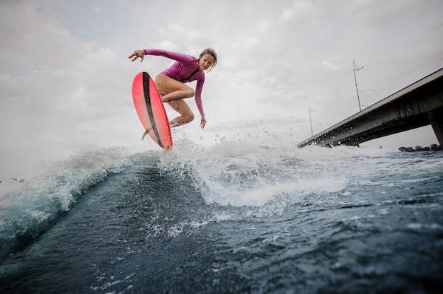 Donna esile attiva che salta sull'onda blu contro il cielo grigio
