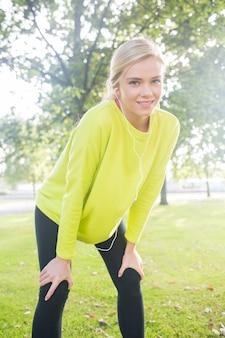 Bionda attiva sorridente che fa una pausa dopo una corsa