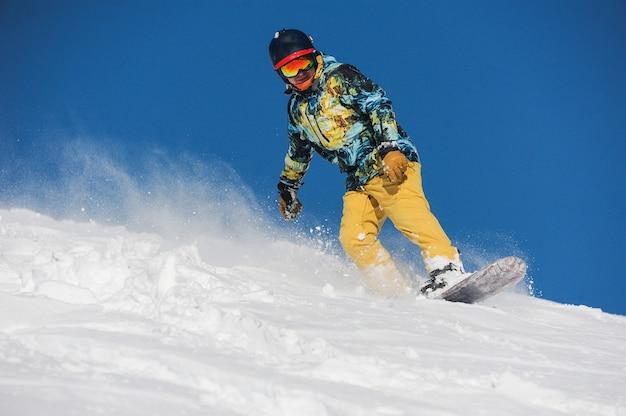 Snowboarder attivo in abbigliamento sportivo luminoso che scende un pendio di montagna in polvere
