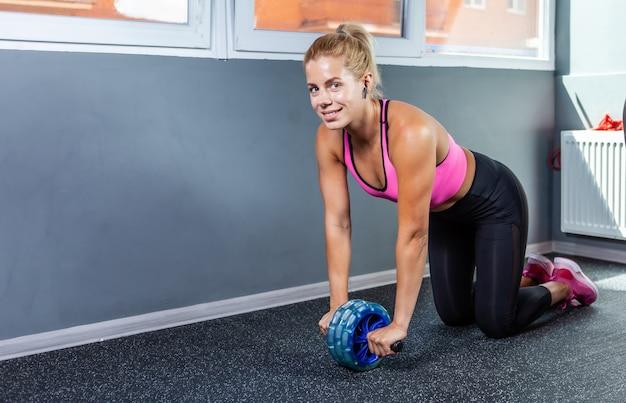 Donna fitness attiva e forte che pratica l'esercizio addominale del rullo ab nella lezione di fitness. concetto dimagrante, stile di vita sano