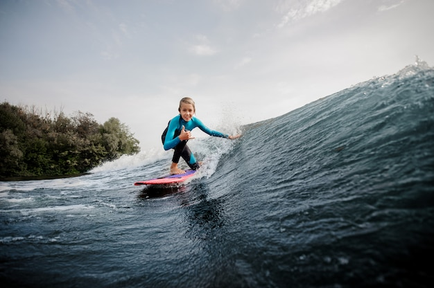 Ragazzo attivo dell'adolescente che sta su un ginocchio sul wakeboard arancio