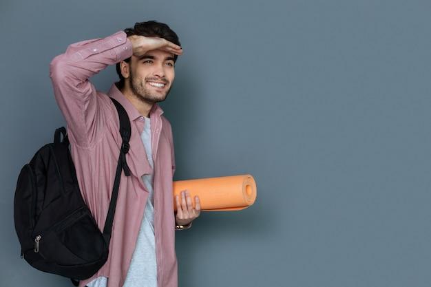 Turismo attivo. bel uomo positivo gioioso che indossa lo zaino e guarda lontano mentre si fa una piacevole passeggiata