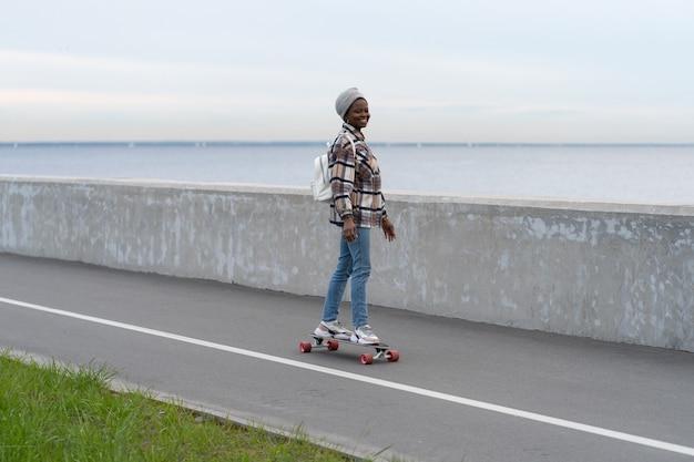 Stile di vita urbano attivo ragazza africana in sella a longboard in riva al mare donna sorridente su skateboard