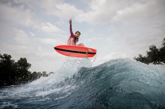 Donna attiva che salta sull'onda di taglio blu contro il cielo grigio
