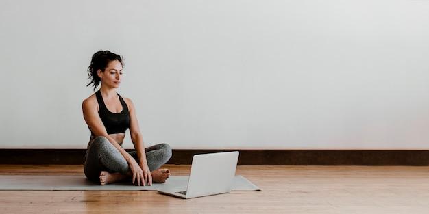 Donna attiva che impara lo yoga online tramite un laptop