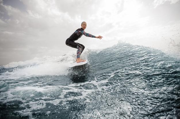 Donna attiva che guida sul wakeboard bianco