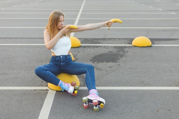 Donna attiva su skaterollers in posa con banana