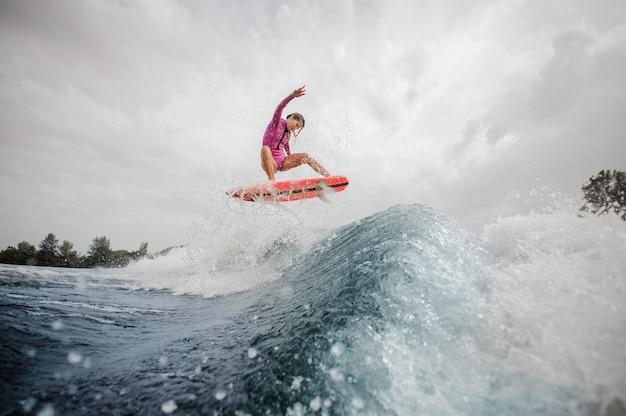 Surfista attivo della donna che salta sull'onda di spruzzatura blu contro il cielo