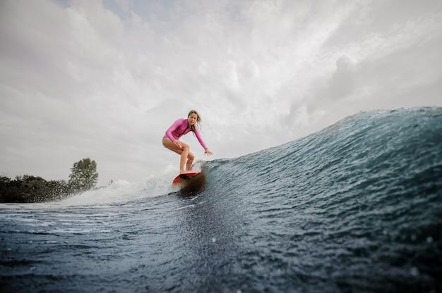 Surfista attivo della donna che guida giù l'onda di spruzzatura blu contro il cielo