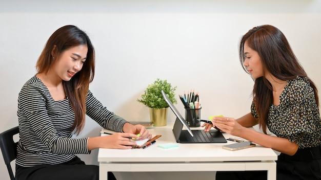 Giovani imprenditrici attive sedute al tavolo della caffetteria utilizzando tablet portatile che si incontrano al bar