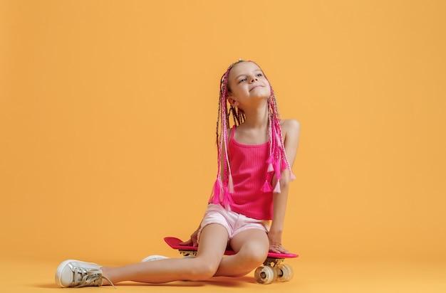 Ragazza attiva in camicia rosa e shorts che si siedono sullo skateboard sopra fondo giallo