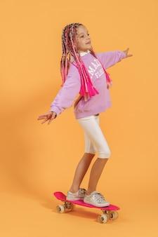 Ragazza attiva in camicia rosa e shorts bianchi che stanno sullo skateboard