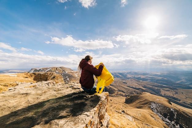 La ragazza attiva si siede sul bordo della scogliera, con uno zaino giallo, gode della natura della montagna e del sole