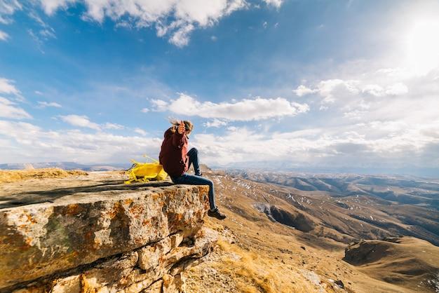 La ragazza attiva si siede sul bordo di una scogliera con uno zaino giallo, gode della natura