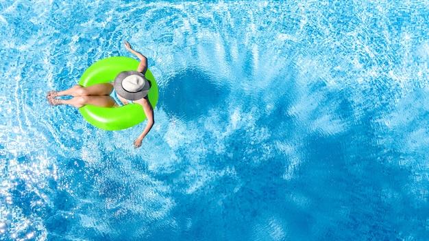 Ragazza attiva in piscina vista dall'alto aerea dall'alto bambino si rilassa e nuota su ciambella ad anello gonfiabile e si diverte in acqua in vacanza in famiglia località di villeggiatura tropicale