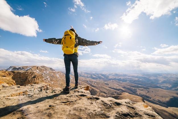 La ragazza attiva viaggia con uno zaino, gode della natura di montagna e del sole