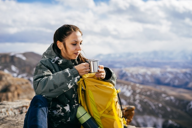 Una ragazza attiva in una giacca calda viaggia attraverso le montagne, gode della natura, beve tè caldo da un thermos