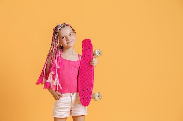Ragazza attiva con i dreadlocks in camicia e shorts rosa con il pennyboard sopra fondo giallo