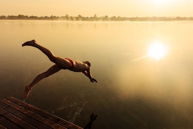 Giovane attivo in costume da bagno rosso che salta in acqua dal molo in legno.