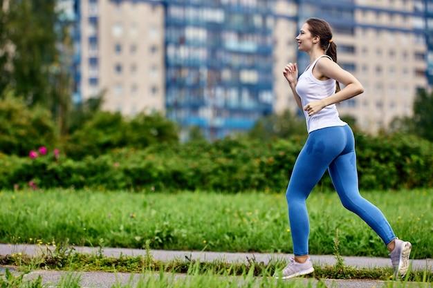 La giovane donna magra attiva corre nel parco in abiti sportivi