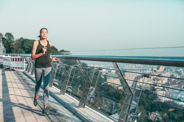 Giovane donna attiva in abiti sportivi che corrono all'aperto in una giornata di sole. modello banner