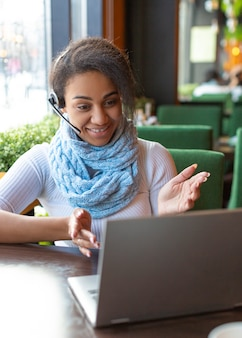 Gesticolando attivamente giovane donna afroamericana mentre incontra i suoi amici in linea.
