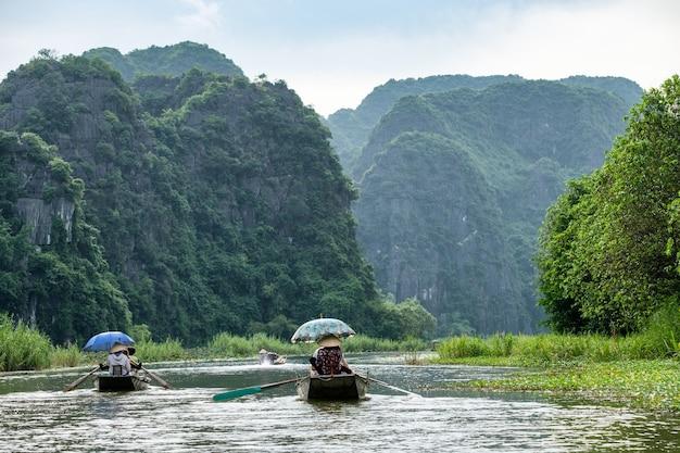 Attività a valle nella valle di montagna in barca con il vietnamita utilizzando la pagaia a piedi nel fiume ngo dong, ninh binh, baia di halong a terra