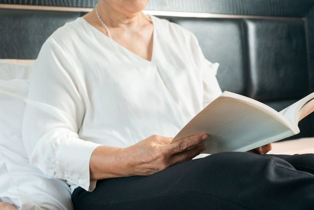 L'attività per la donna senior ha letto un libro per evitare rischi