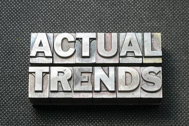 Frase di tendenze reali composta da blocchi di stampa tipografica metallici su superficie perforata nera