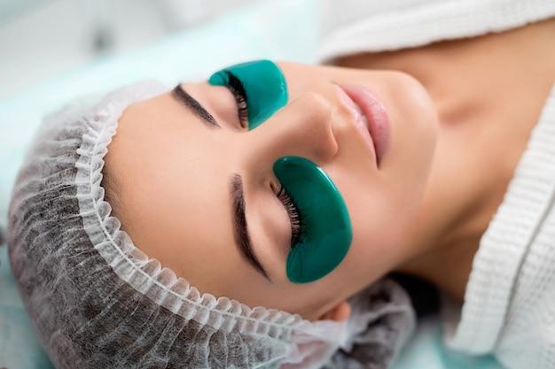 Digitopressione, massaggio alle tempie, collagene a scaglie verdi procedura cosmetica, viso della donna con scaglie verdi sotto gli occhi.