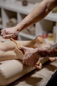 Digitopressione, riflessologia. la medicina naturale, la riflessologia, il massaggiatore per i piedi con digitopressione opprimono i punti del flusso di energia.