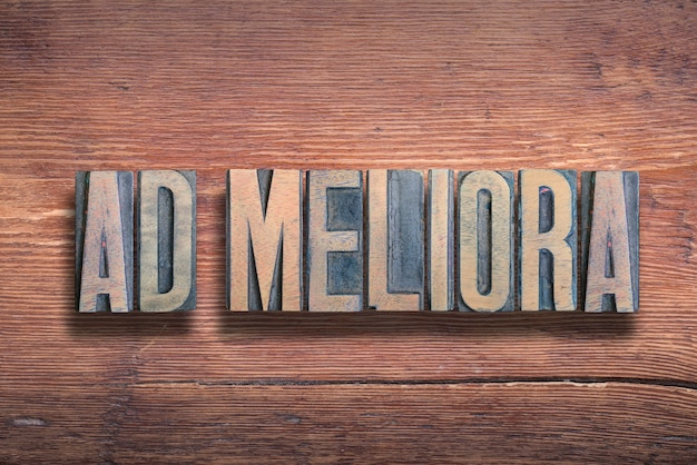 Ad meliora antico significato del detto latino - verso cose migliori, combinato su una superficie in legno verniciato vintage
