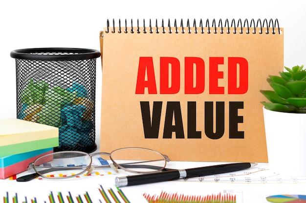 Valore aggiunto su blocco note, grafico, bicchieri. concetto di affari.