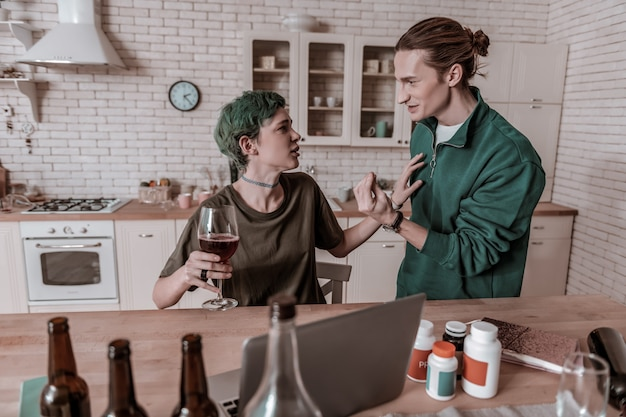 Dipendente dall'alcol. bel ragazzo emotivo arrabbiato con la sua ragazza dipendente dall'alcol